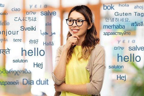 translation, education and people concept - happy asian woman in glasses or student over greeting words in different foreign languages